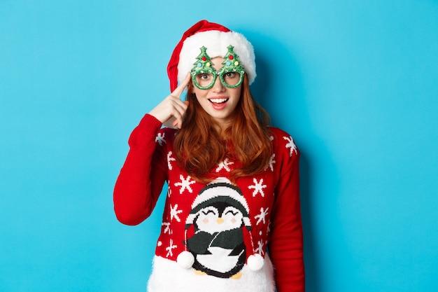 즐거운 휴일과 크리스마스 개념. 새 해를 축 하 하 고, 산타 모자와 파티 안경, 파란색 배경에 서있는 재미있는 빨간 머리 십 대 소녀.