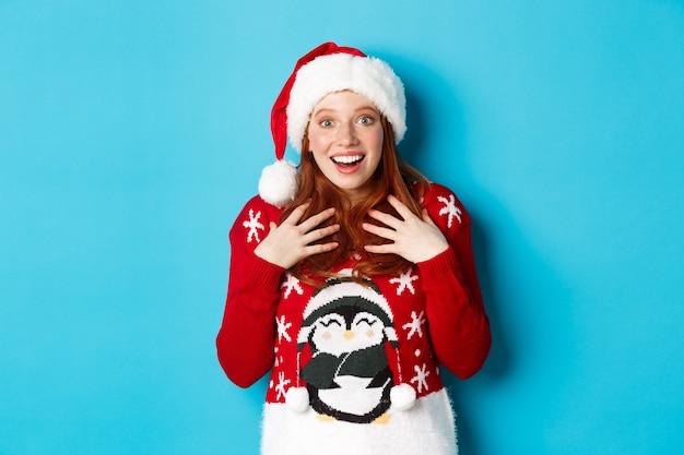 즐거운 휴일과 크리스마스 컨셉입니다. 예상치 못한 선물을 받고 놀란 빨간 머리 소녀는 깜짝 놀라 숨을 헐떡이며 유쾌한 불신으로 쳐다보며 파란색 배경에 산타 모자를 쓰고 서 있습니다.