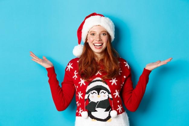 Buone vacanze e concetto di natale. ragazza rossa allegra con cappello da babbo natale e maglione natalizio, alzando le mani sugli spazi di copia, tenendo qualcosa su sfondo blu.