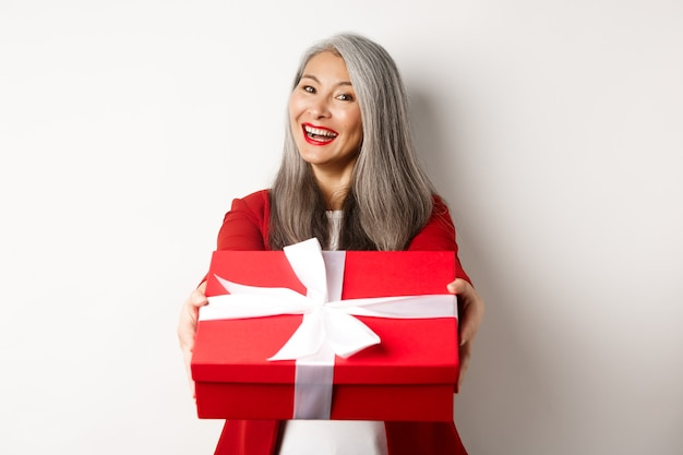 幸せな休日のコンセプト。あなたに赤いギフトボックスを与え、笑顔、バレンタインデーを祝って、白い背景の上に立っている陽気なアジアの年配の女性。