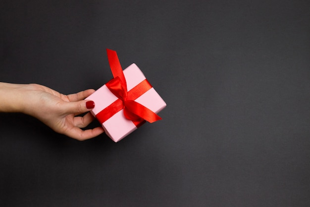 Happy holidays concept with female hand hold surprise gift with red atlas ribbon on dark background