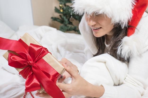 ハッピーホリデー!女性の手は白いベッドでクリスマスのギフトボックスの弓を解きます。