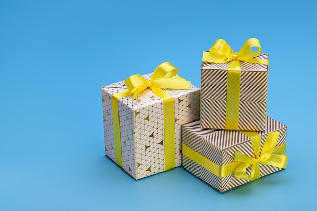 Счастливых праздников. подарочные коробки с узорами, желтая лента с бантом на синем фоне. новогоднее и рождественское настроение.