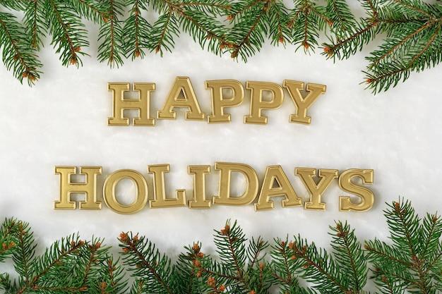 幸せな休日の黄金のテキストと白い背景の上のトウヒの枝