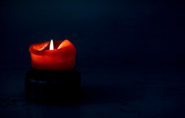 幸せな休日のグリーティングカードの背景と冬のシーズンのコンセプト暗い背景の赤い休日のキャンドル高級ブランドのデザインとクリスマスの大晦日とバレンタインデーの装飾