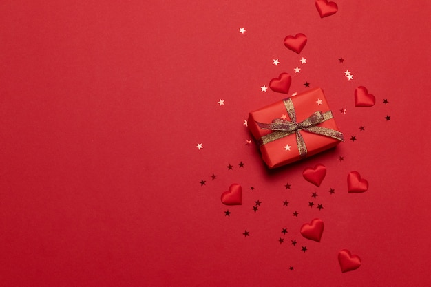 スターゴールドキラキラとハッピーホリデーグリーティングカードは、赤の背景にギフトボックスと紙吹雪を輝きます。
