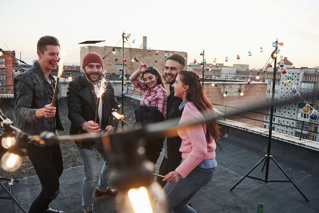 Happy holidays. playing with sparklers on the rooftop. group of young beautiful friends