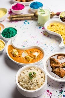 Концепция happy holy, показывающая индийское ассорти из обеденных блюд, таких как куриное масло для панир, масала, рис, наан джира, черный чана, жареный джалеби рас, малай тхандай и фарсан с цветами холи и пичкари