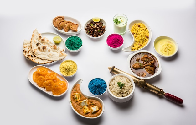 Happy holy concept  showing indian assorted lunch food like chicken paneer butter masala naan jeera rice black chana fry jalebi ras malai thandai and farsan with holi colours and pichkari