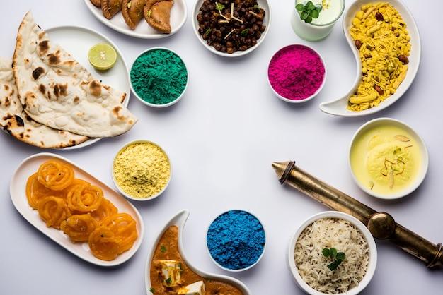 パニールバターマサラナンジーラライスブラックチャナフライジャレビラスマライタンダイやファーサンなどのインドのランチフードの盛り合わせをホーリー色とピッカリで示すハッピーホーリーコンセプト