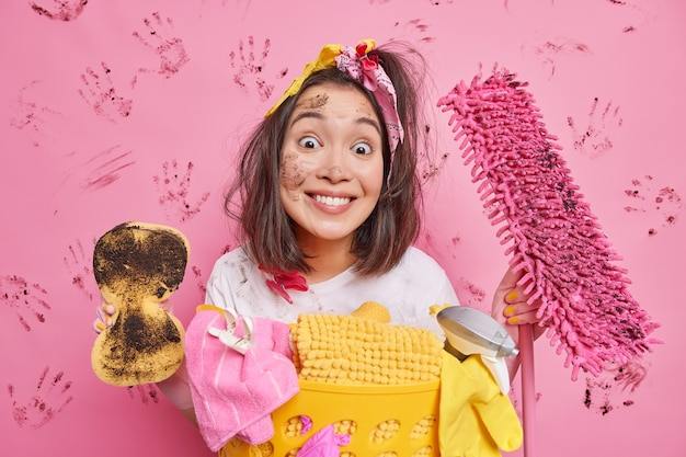 Happy homemaker looks gladfully at you smiles toothily holds sponge and mop does spring cleaning of house cleans up apartment smeared with dirt poses near laundry basket isolated on pink