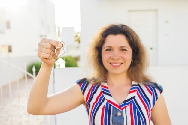 행복한 집주인이나 세입자가 열쇠를 보여주고 당신을 바라보고 있습니다.