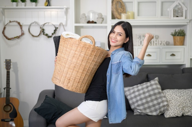 Happy housekeeper carrying a bucket cloths for laundry in the house