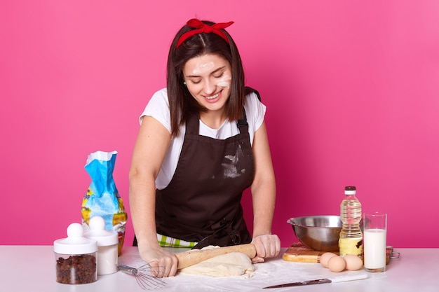 Happy housewife or baker holds baking rolling pin and rolls out dough with enjoyed facial expression