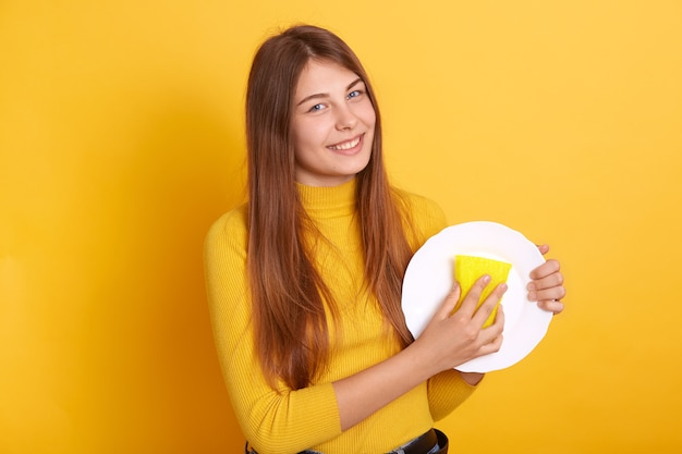 Happy housewife demonstrating washing process, holding white plate and sponge in hands and , wearing casual attire