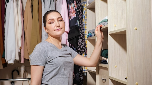 Happy housewife in grey t-shirt puts folded clean clothes on different wooden shelves in contemporary light walk-in closet at home closeup