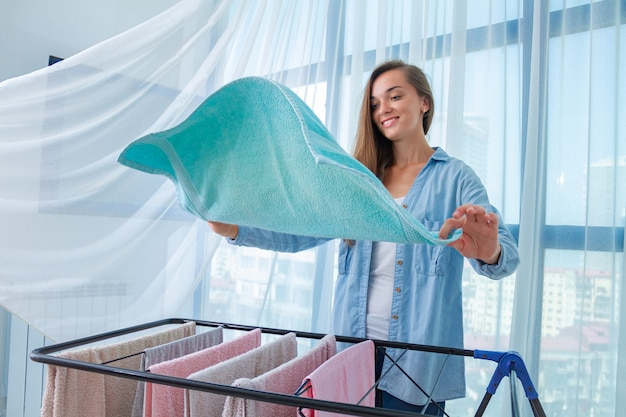 Happy housewife hangs wet linen on the clothes dryer after laundry at home. household chores and housekeeping