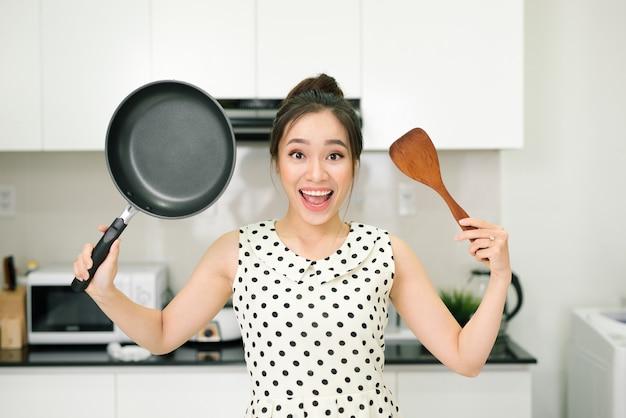 幸せな主婦は台所で鍋の木製のターナーで持ちこたえます