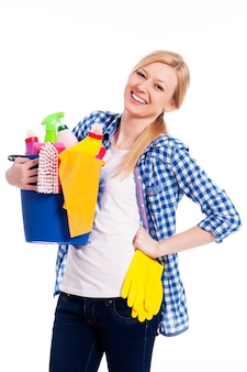 Счастливая домохозяйка, держащая уборочное оборудование