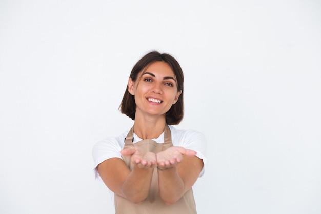 白で隔離されるエプロンを着た幸せな主婦は、空のスペースで前に手を握る