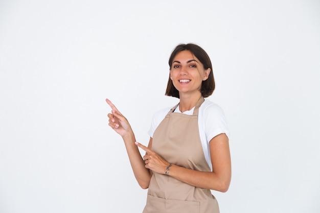 Счастливая домохозяйка в фартуке, изолированная на белом указательном пальце слева