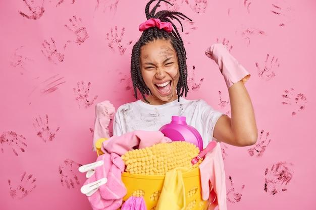 행복한 주부는 예 제스처를 쥐고 주먹을 집안 청소를 축하하며 세탁 바구니 근처에 고무 장갑 스탠드를 착용합니다. 더러운 분홍색 벽에 고립 된 재미