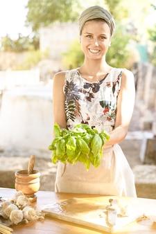 典型的な地中海料理を準備するバジルの束と屋外で幸せな主婦