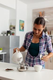 朝の朝食に緑茶を準備するためにティーポットにお湯を注ぐ幸せな主婦