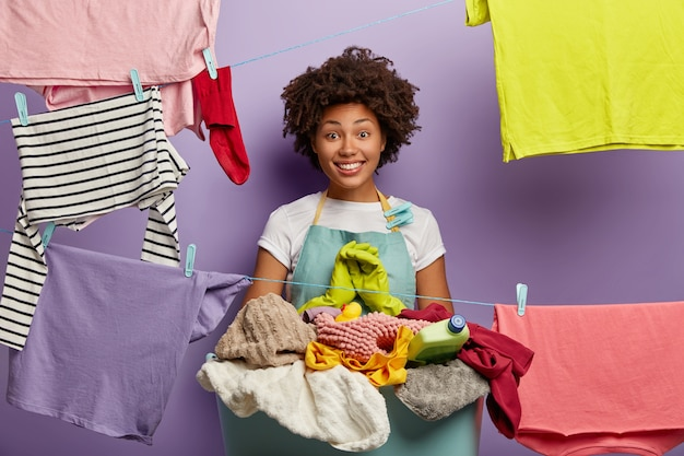 Happy housewife satisfied to finish domestic work in time, busy doing washing, stands near heap of unfolded dirty linen in basket, dressed in casual blue apron. cleaning day and daily routine concept
