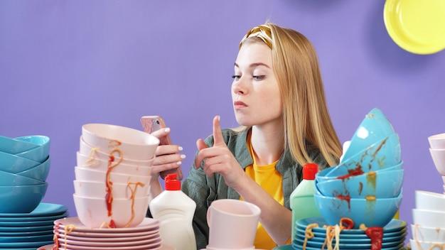 Счастливая домохозяйка показывает палец вверх, держа мобильный телефон