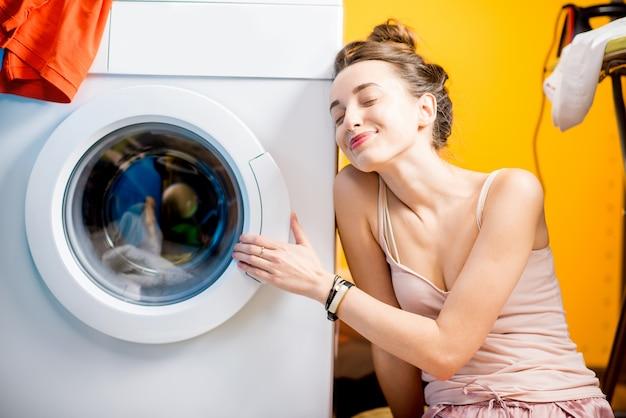 Счастливая домохозяйка, сидя возле стиральной машины дома