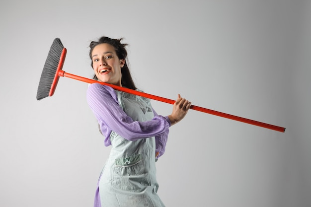 Happy housewife with a broom
