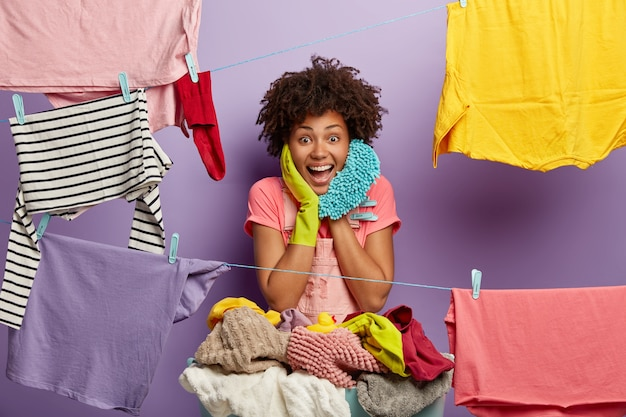 Happy housewoman hangs clean laundry on clothes line, does washing at home, busy with household duties holds mop, wears t shirt and rubber gloves, dries clothes, pegs out washing, smiles broadly