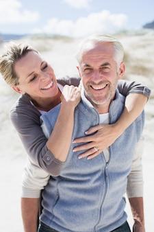 カメラを見てビーチで幸せな抱擁のカップル