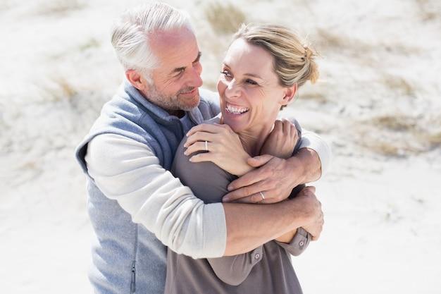 お互いを見てビーチで幸せな抱擁のカップル