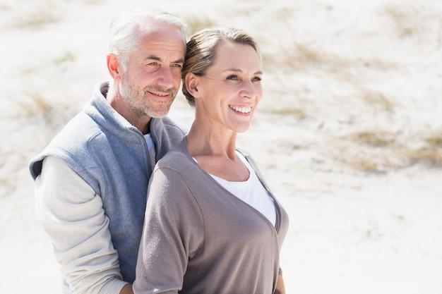 幸せな抱擁のカップルは、離れて見るビーチに