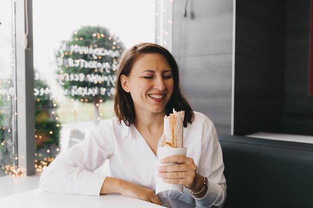 Счастливая голодная позитивная девушка, молодая женщина, сидящая в кафе, ест шаурму в лаваше