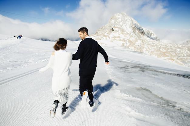 幸せな夫と妻は雪の中でどこかを走っています