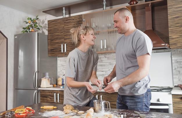 행복한 남편과 아내는 부엌에서 쿠키를 만들면서 서로를보고 웃습니다. 좋은 가족 관계. 공동 음식 준비