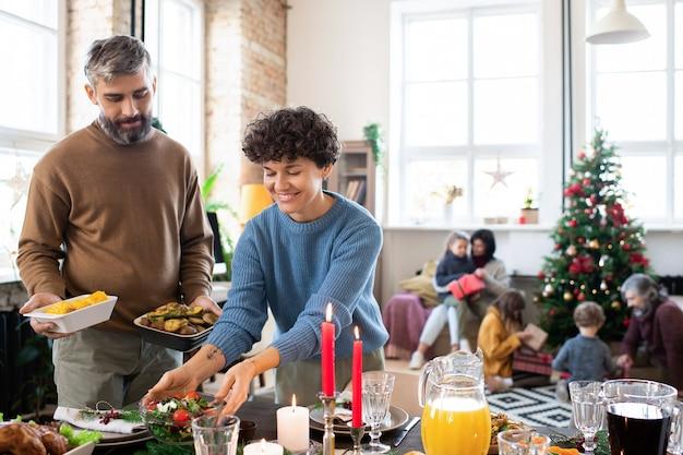 Счастливые муж и жена кладут домашний салат, печеный картофель, напитки и другую еду на праздничный стол перед семейным рождественским ужином