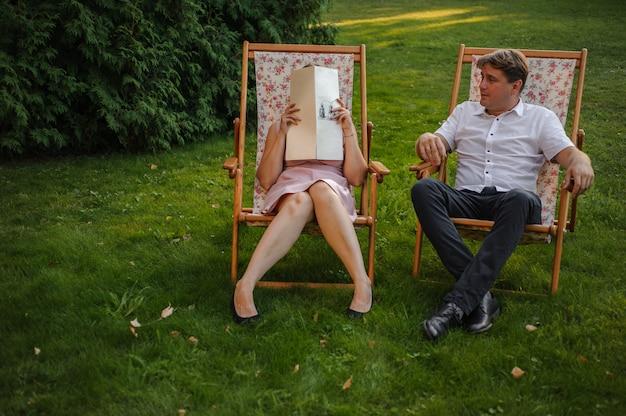 Счастливый муж и жена сидит на шезлонге в зеленом парке на gazon