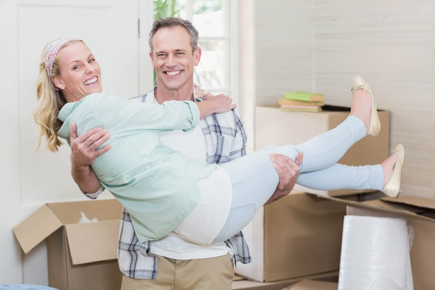 Happy husband carrying his wife in their new house