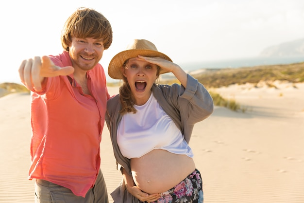Happy husband and pregnant wife having fun on beach