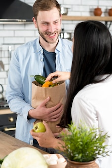 Happy husband standing kitchen holding brown grocery bag