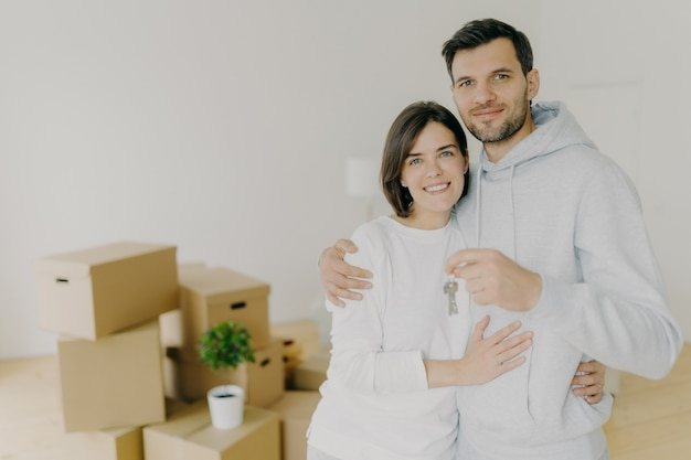 Happy husband and wife buy real estate, cuddle and hold keys, stand in living room with boxes in new home