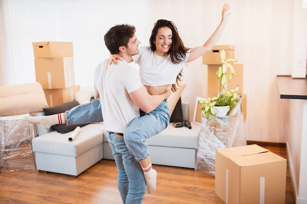 Happy husband and wife have fun swirl sway relocating to own apartment together, relocation concept. overjoyed young couple dance in living room near cardboard boxes entertain on moving day,