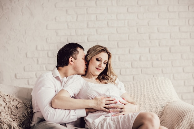 Happy husband and wife sitting on sofa in living room