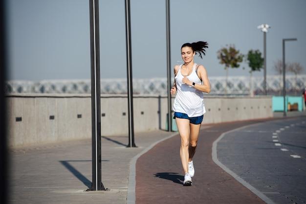 야외에서 새로운 트랙을 달리는 행복한 운동 여성