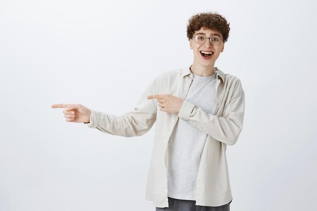 Счастливый впечатленный парень-подросток позирует у белой стены