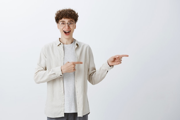 Happy impressed teenage guy posing against the white wall
